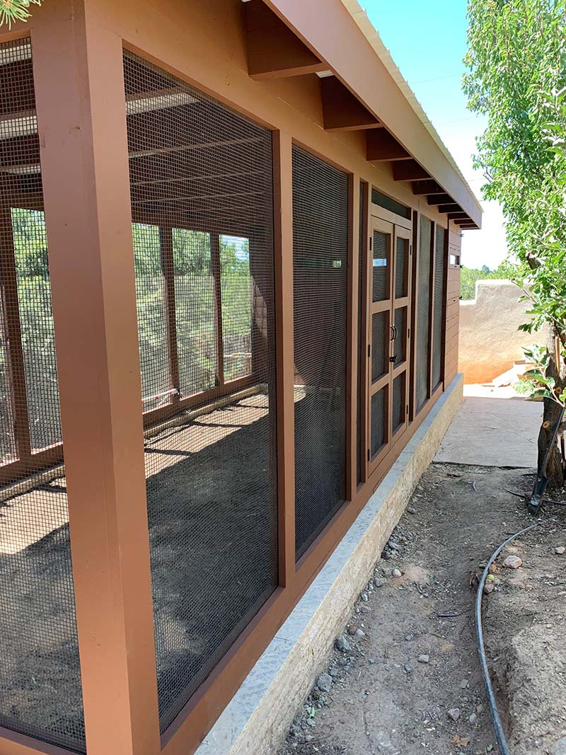 Side of the run of a custom modern chicken coop with two sets of double doors in Santa Fe, NM