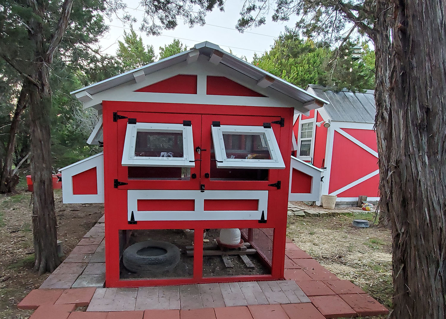 Back of 6'x4'x18′ American Coop painted red with white trim with extra egg hutch