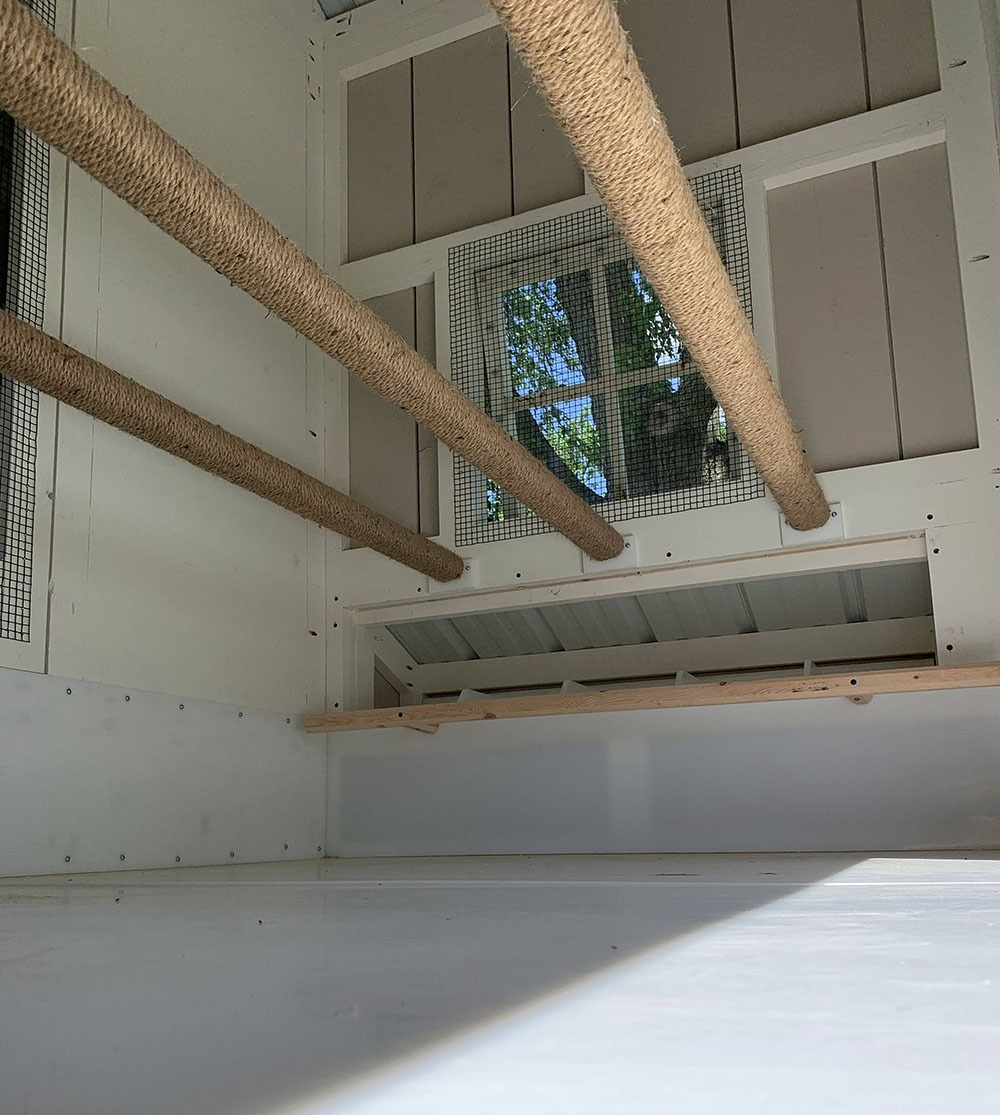 Inside the 5'x10′ henhouse of a 10'x40′ Craftsman Coop with 3 roostbars and a 5-gang egg hutch